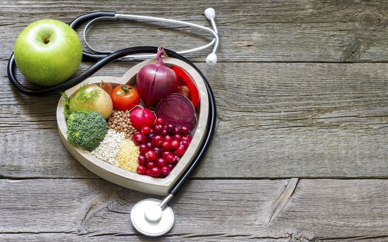 Stethoscope curled around heart shaped healthy eating platter
