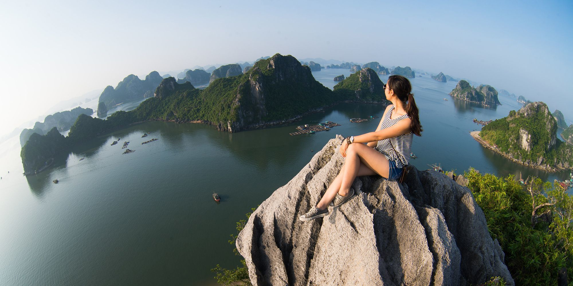 girl sitting on rock in Halong Bay Vietnam