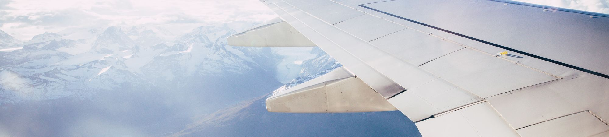 plane wing in sky over snowy mountains and lake