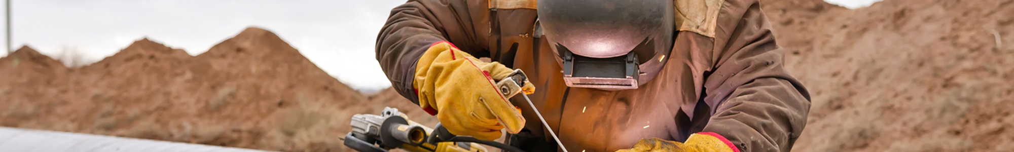 Boilermaker welder working on a pipeline wearing safety gear