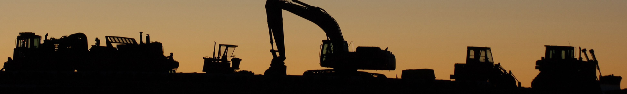 Silhouette of construction plant equipment excavators rollers final trim at sunset