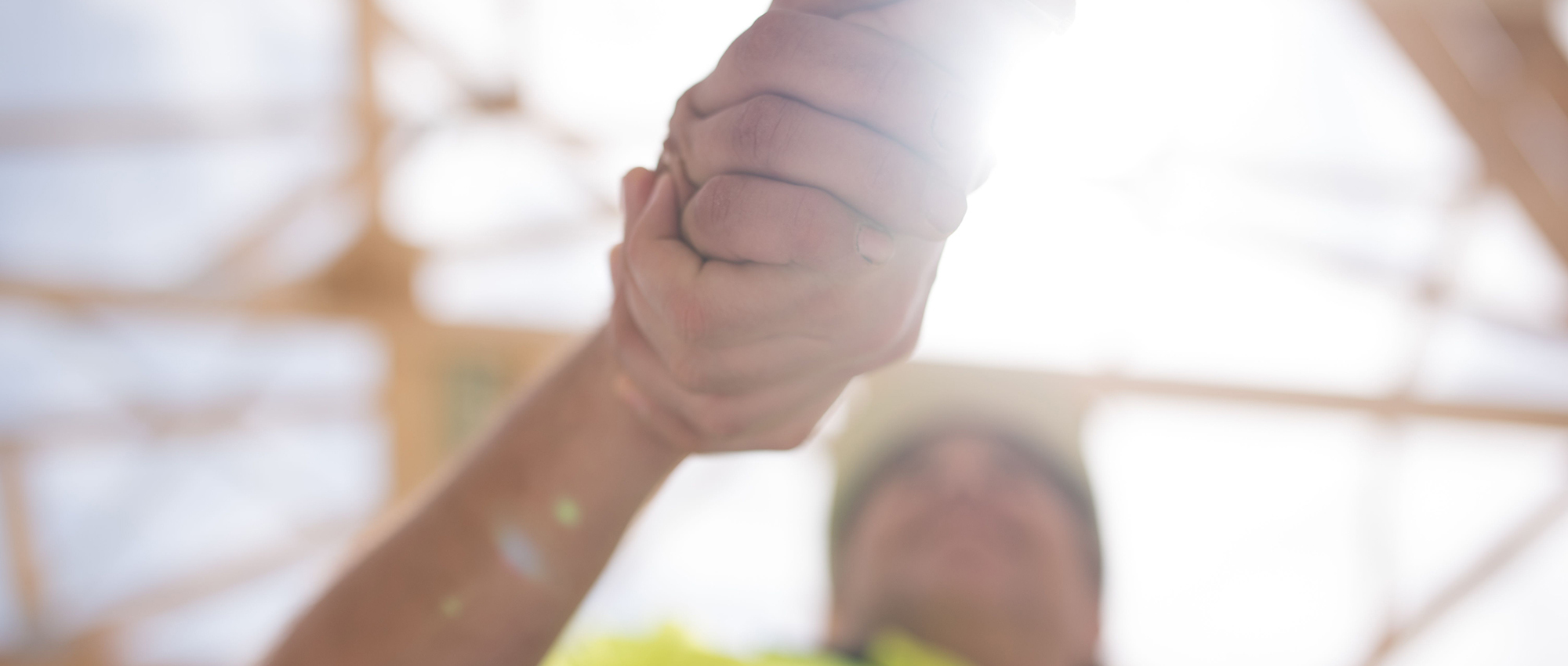 Two construction workers shaking hands on a residential construction site