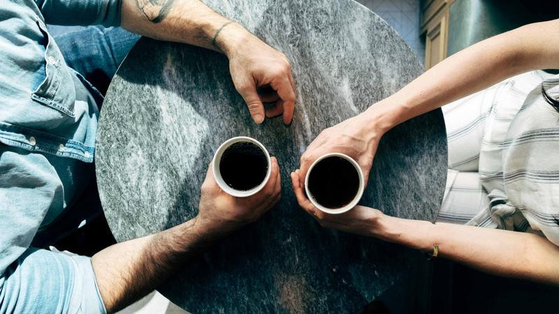 birds eye view of man and woman with coffee on marble table