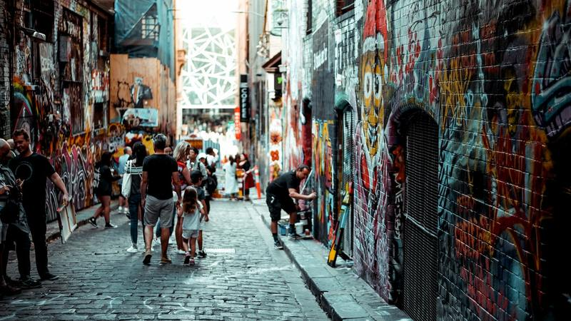 tourists walking down a graffiti alley in melbourne