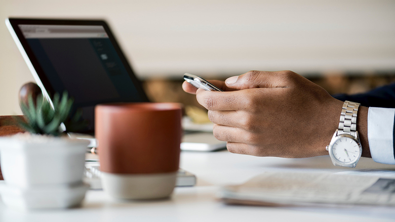 Hand holding a phone above a desk with a newspaper, plant, coffee and laptop