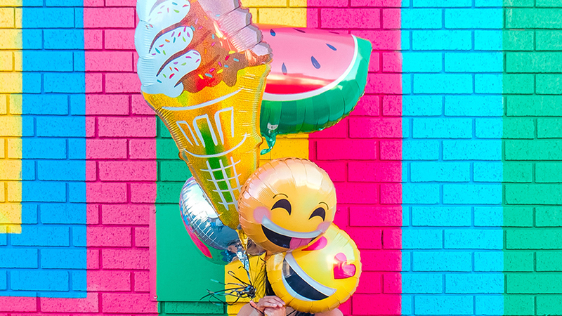 Emoji balloons in front of a striped colourful brick wall