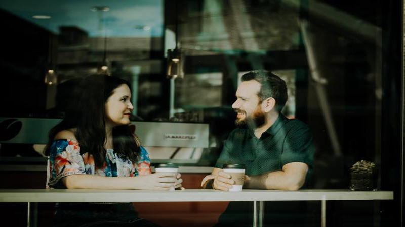 man and woman talking in cafe with coffee