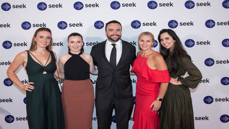 TMS Talent sydney team posing in front on branded seek sign at seek awards