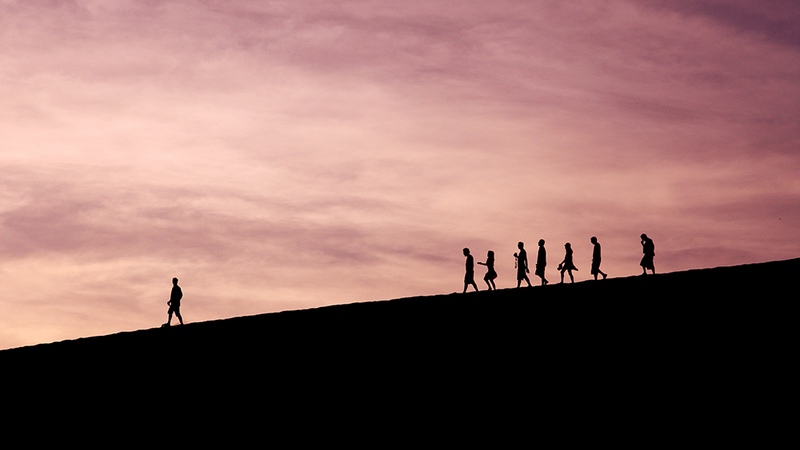 Group of people walking down a hill with a leader