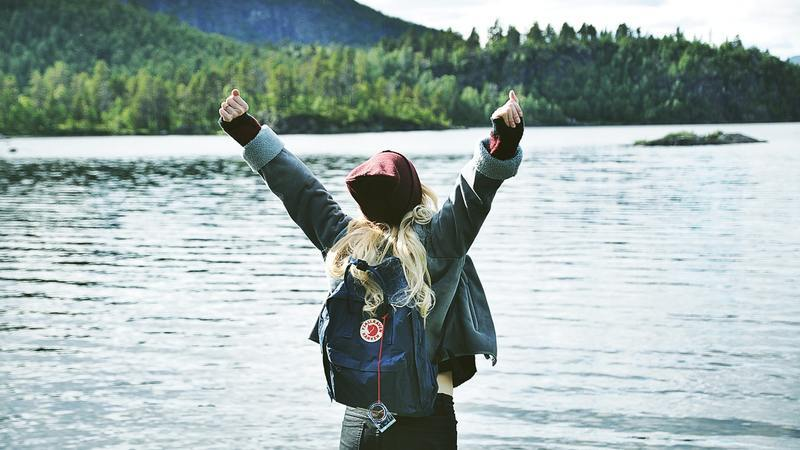 female traveller wearing backpack with her arms in the arm looking over a lake