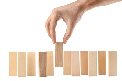 Alt = hand placing a wooden domino