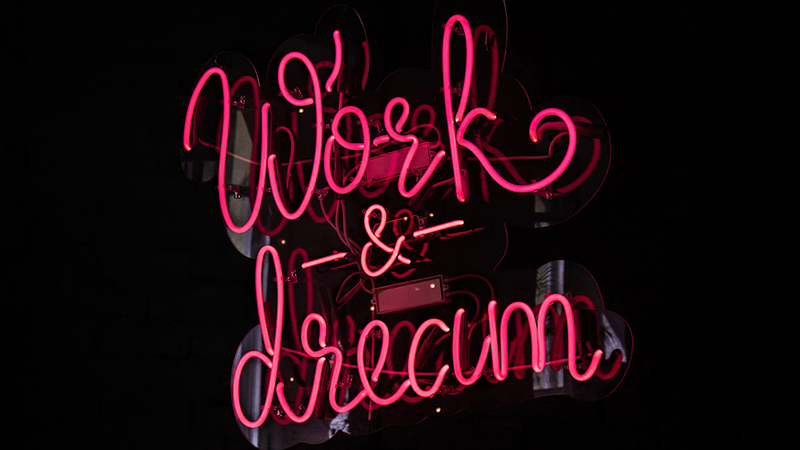 PInk neon sign reading 'work & dream'