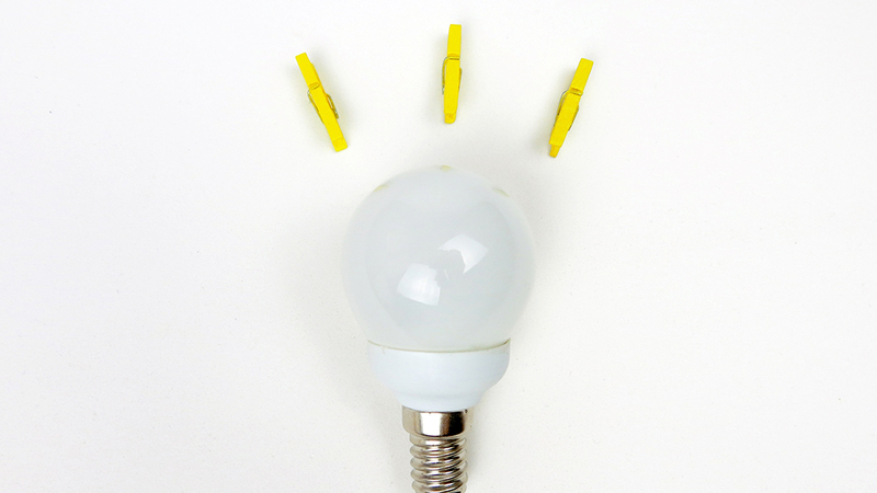 Light bulb and three yellow pegs