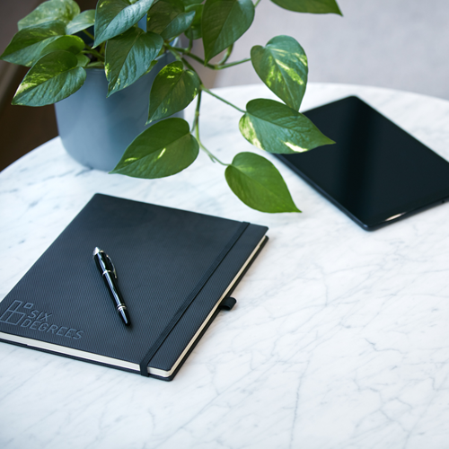 black book and pen on a marble table with a plant