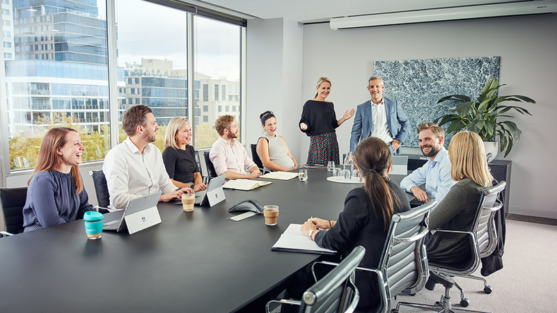 People around a boardroom table laughing and smiling