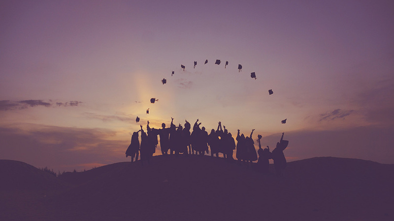 Silhouette of graduates throwing hats