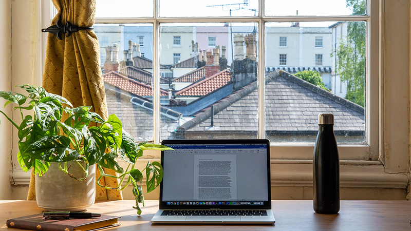 Laptop on a desk in front of a window overlooking rooftops